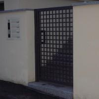 Eingangstor mit überkreuz vernieteten Flachstäben, Briefkasten als Mauerdurchwurfbriefkasten